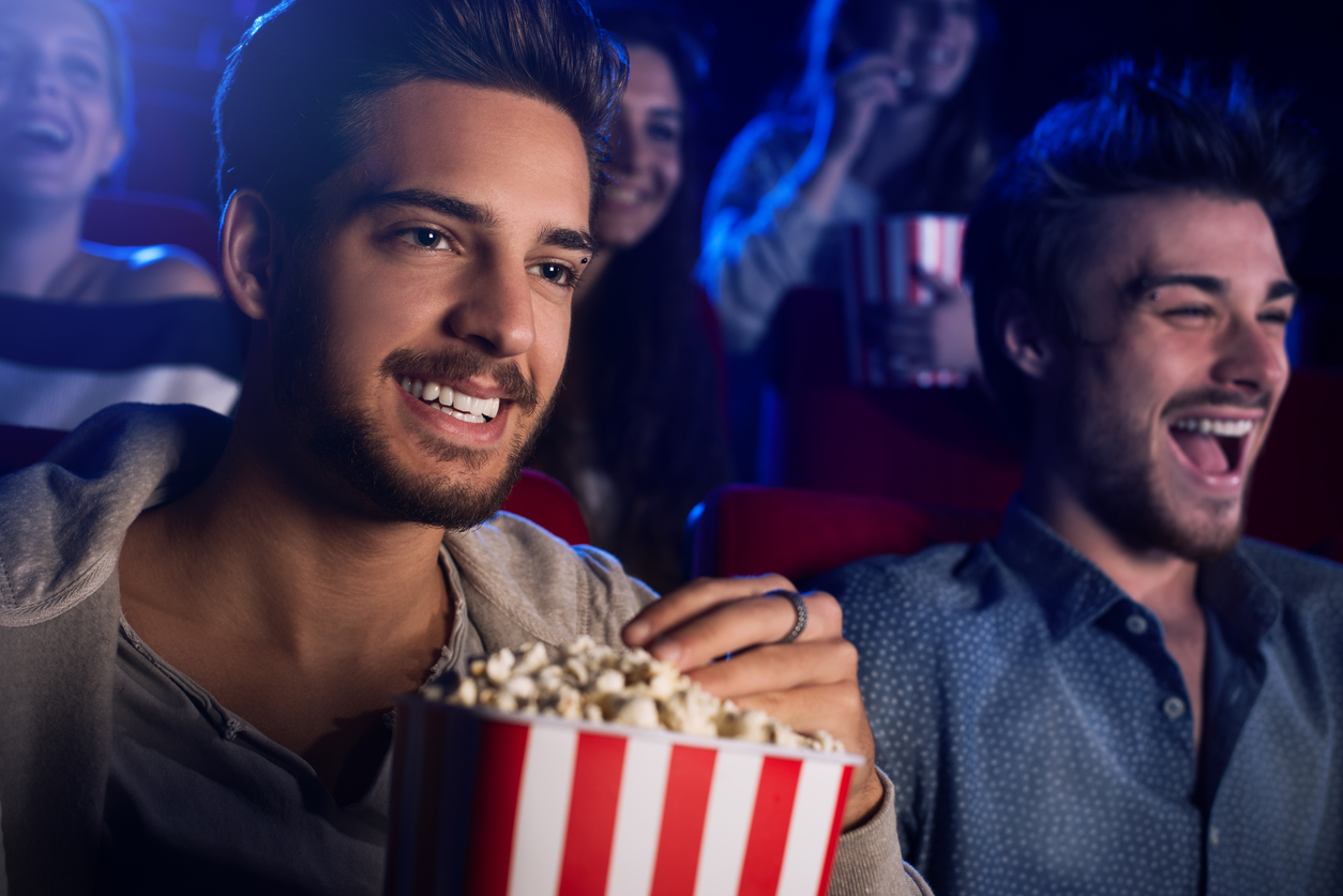 Young gay couple sitting at the cinema, watching a movie and eating popcorn.